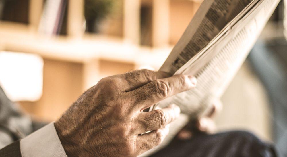 Zeitungsleser informiert sich über Geld Invest Anlagemöglichkeit Diamant
